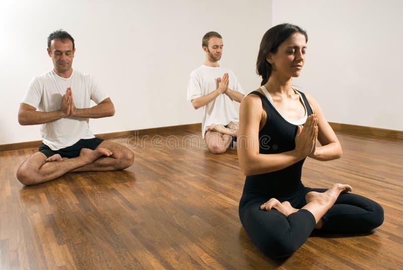 Due uomini e un'yoga di pratica della donna - orizzontale immagine stock