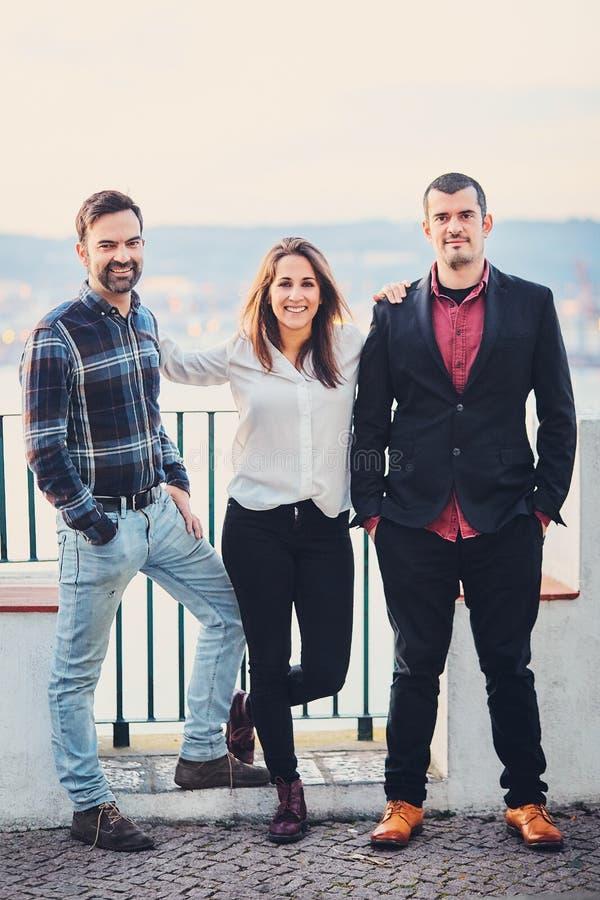 Due uomini ed una donna stanno stando accanto al sorriso e lo scherzo, si diverte Gli amici ridono dei precedenti della città di  immagini stock libere da diritti
