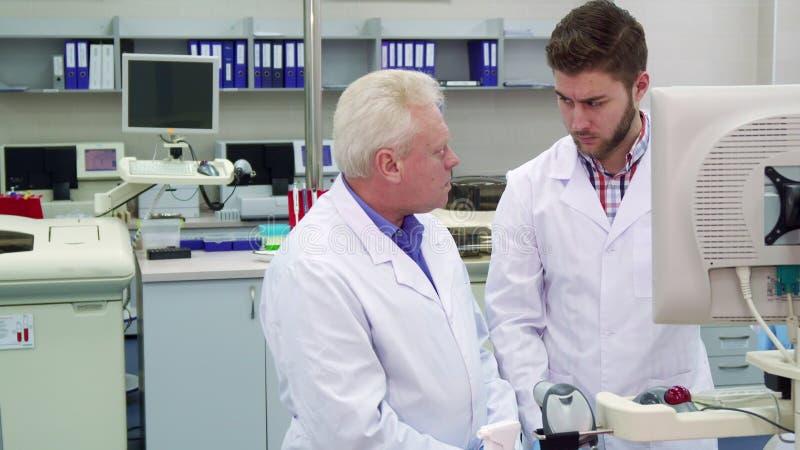 Due uomini esaminano il monitor il laboratorio fotografie stock