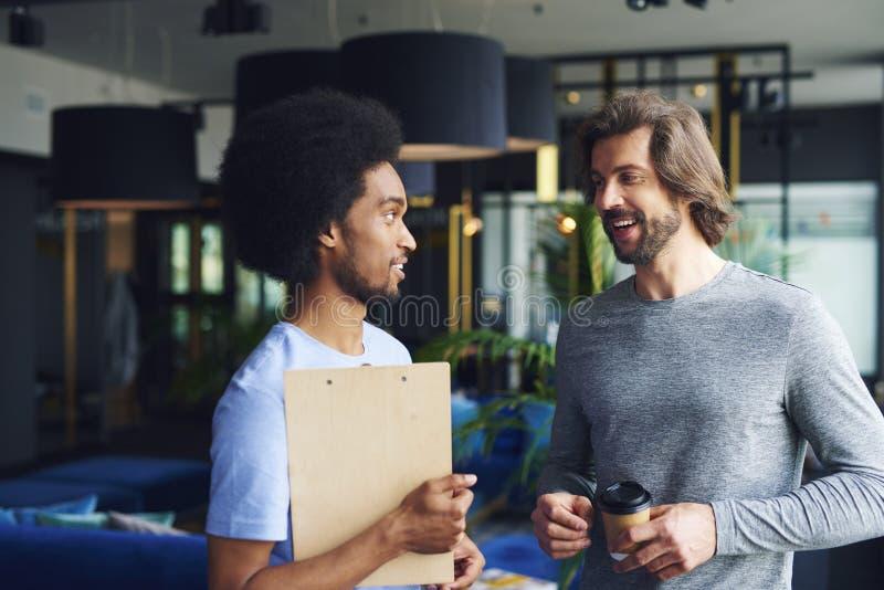 Due uomini felici che discutono sul lavoro fotografie stock libere da diritti