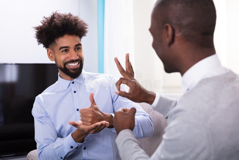 Due uomini felici che fanno linguaggio dei segni immagini stock