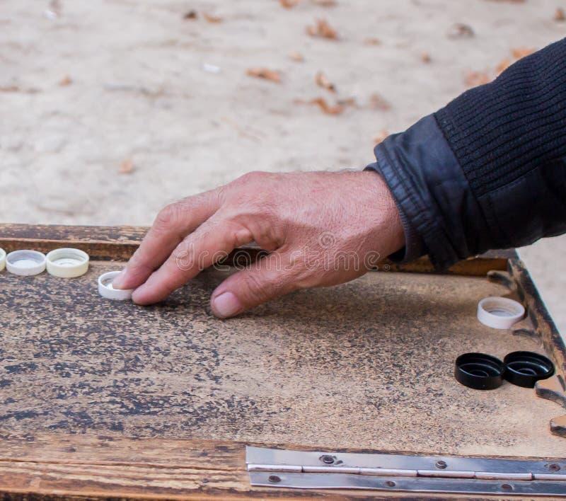 Due uomini giocano per strada giocando a backgammon in autunno fotografia stock libera da diritti