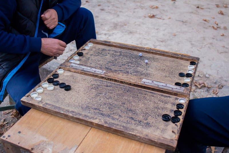 Due uomini giocano per strada giocando a backgammon in autunno fotografie stock libere da diritti