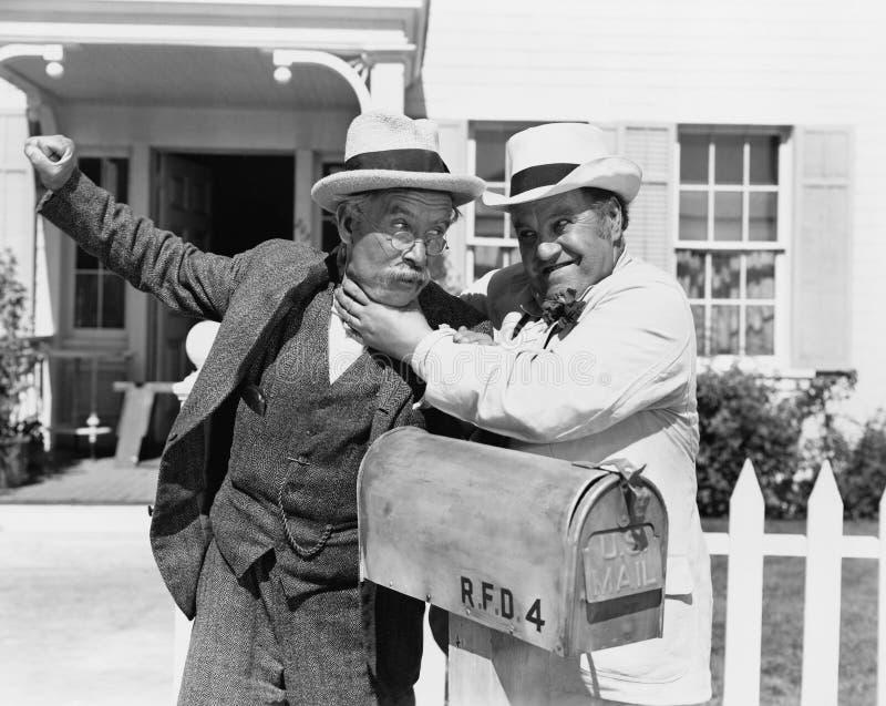 Due uomini maturi che combattono vicino ad una cassetta delle lettere davanti ad una casa (tutte le persone rappresentate non son fotografie stock