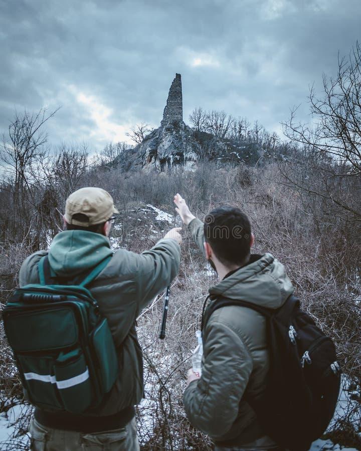 Due uomini nel legno con uno zaino, hanno trovato uno ston sconosciuto immagine stock