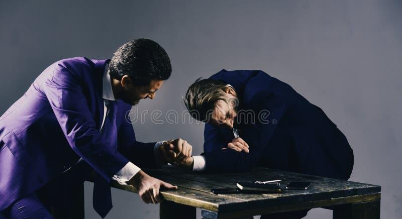 Due uomini o uomini d'affari che lottano con le armi, lotta per direzione fotografie stock