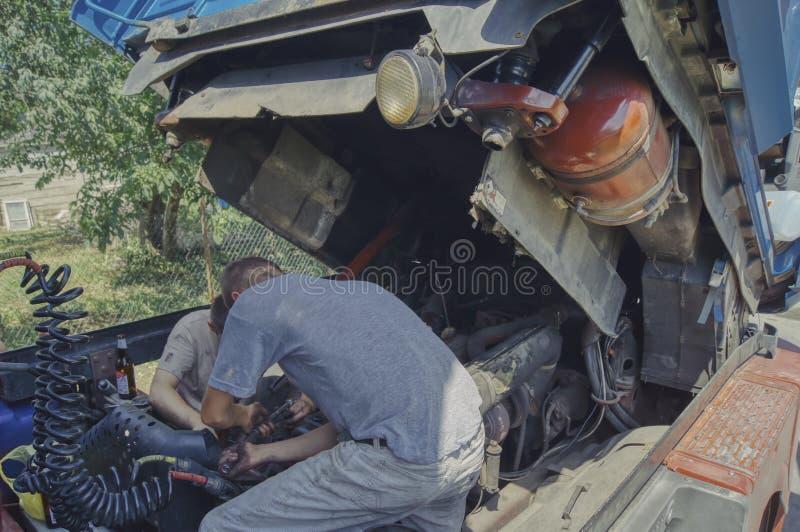 Due uomini riparano il camion, lavorano per logorare un giorno caldo fotografie stock