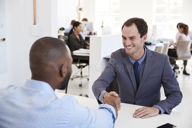 Due uomini si siedono e stringono le mani ad una riunione in un ufficio fotografie stock