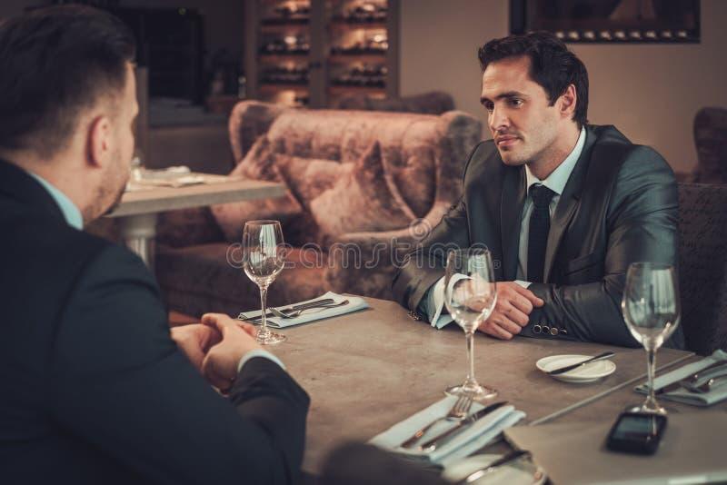 Due uomini sicuri di affari hanno pranzo di lavoro al ristorante fotografia stock libera da diritti