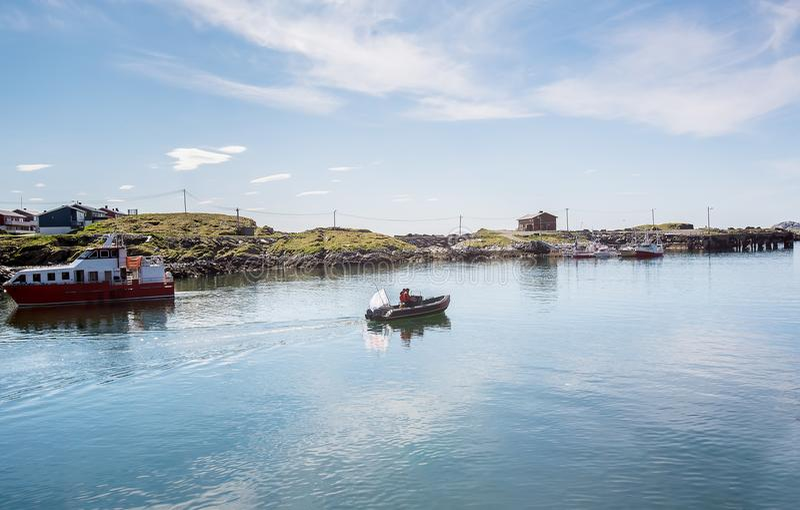 Due uomini in una navigazione dell'imbarcazione a motore lungo la baia Pesca marittima Norw immagini stock