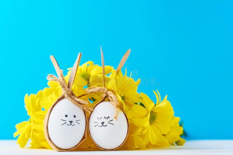 Due uova con i fronti del disegno con i fiori gialli su un fondo blu fotografia stock