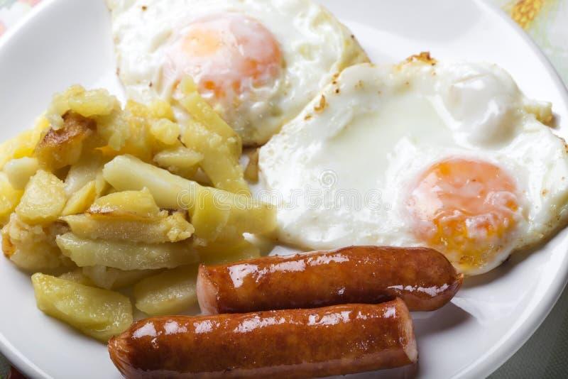 Due uova con le patate e le salsiccie fritte fotografie stock libere da diritti