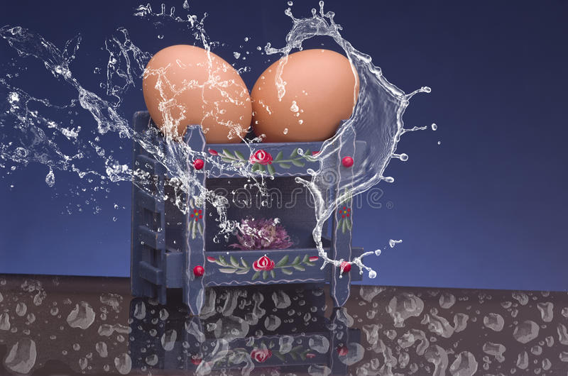 Due uova crude che spruzzano dall'acqua sul fondo nero e blu Uova nel letto di cuccetta fotografie stock