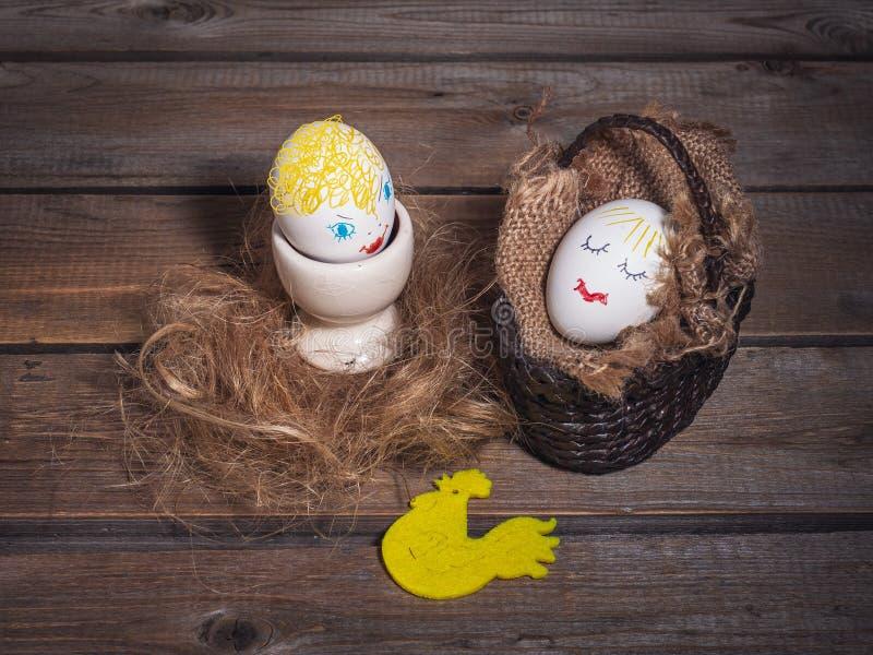Due uova divertenti con i fronti dipinti su fondo di legno Telefono mobile giallo fotografia stock libera da diritti