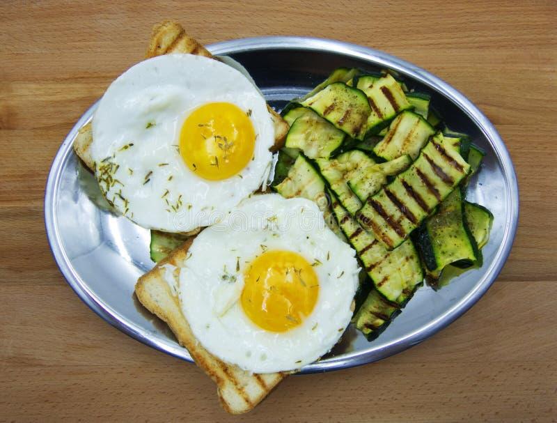 Due uova fritte con lo zucchini arrostito ed il pane tostato fotografie stock