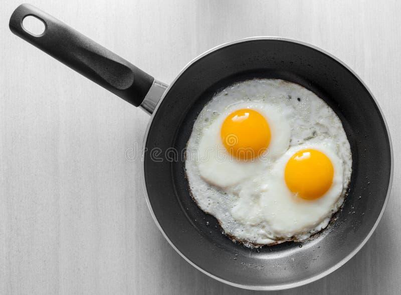 Due uova rimescolate in padella nera fotografia stock