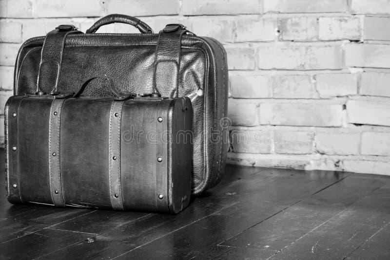 Due valigie di cuoio sul muro di mattoni in bianco e nero Retro monocromio di progettazione del bagaglio Concetto di turismo e di immagini stock