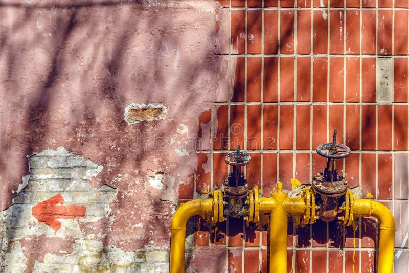 due valvole gialle sui tubi sulla parete di un edificio alto fotografia stock