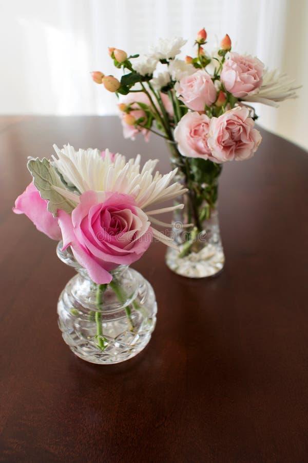 Due vasi a cristallo con le rose ed i fiori miniatura fotografia stock libera da diritti