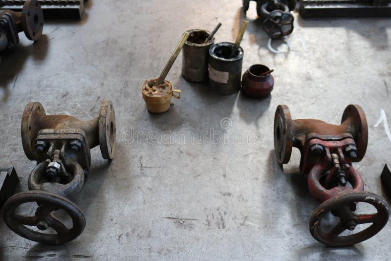 Due vecchi fermi del metallo, accessori per tubi, latte con il grasso della grafite, solidol su una grande tavola del ferro nella fotografie stock