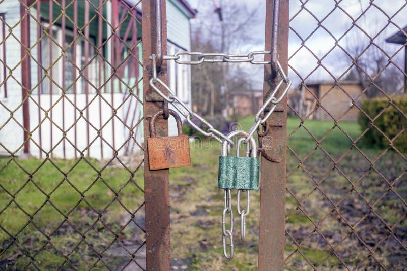 Due vecchi lucchetti e una catena su un recinto arrugginito fotografia stock