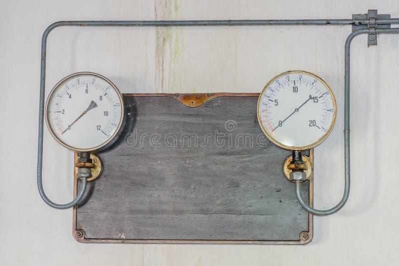 Due vecchi manometri su un di piastra metallica fatto del ghisa fotografia stock