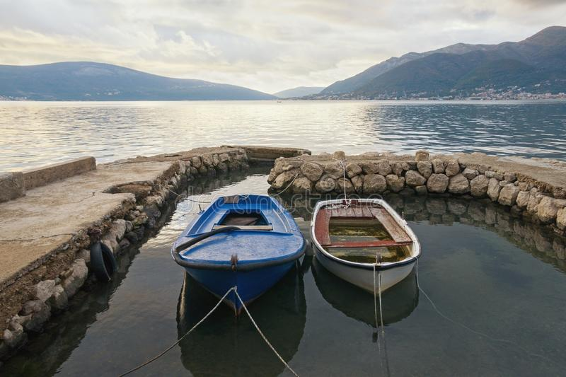 Due vecchi pescherecci in piccolo porto il giorno nuvoloso di autunno Il Montenegro, baia di Cattaro fotografie stock