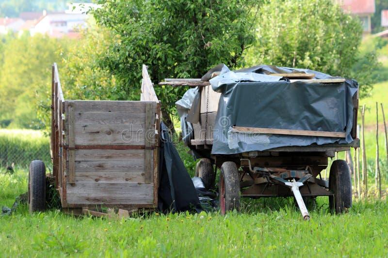 Due vecchi rimorchi di trattore di legno dilapidati rustici con quattro e due gomme coperte di nylon spesso lasciato in cortile c fotografia stock