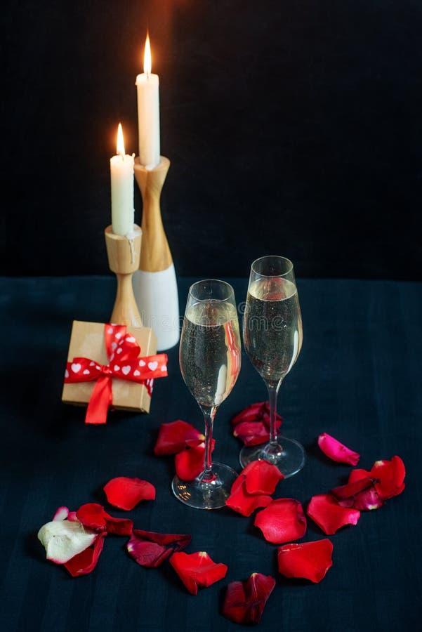 Due vetri con champagne, il contenitore di regalo ed i petali bianchi delle rose rosse sui precedenti delle candele immagine stock