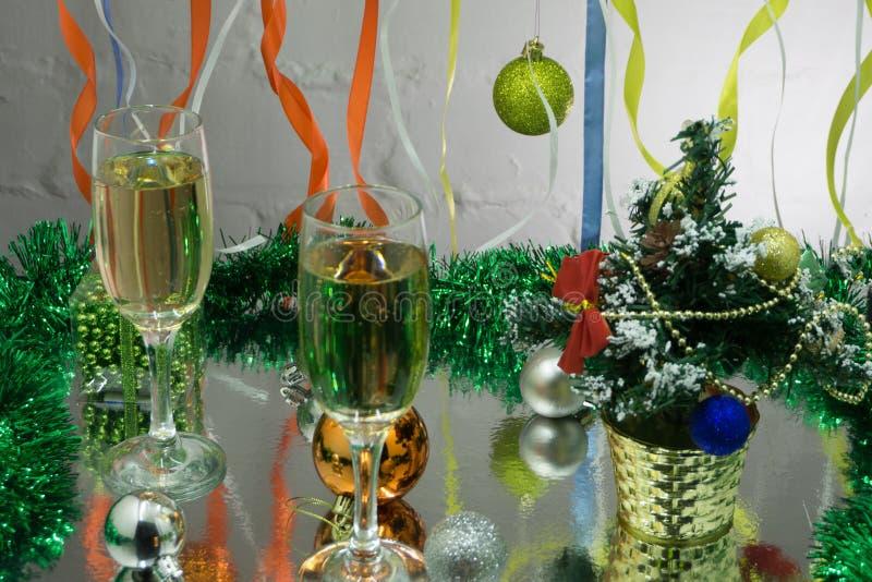 Due vetri con champagne sulla tavola sull'albero di Natale e sul fondo del camino fotografia stock libera da diritti