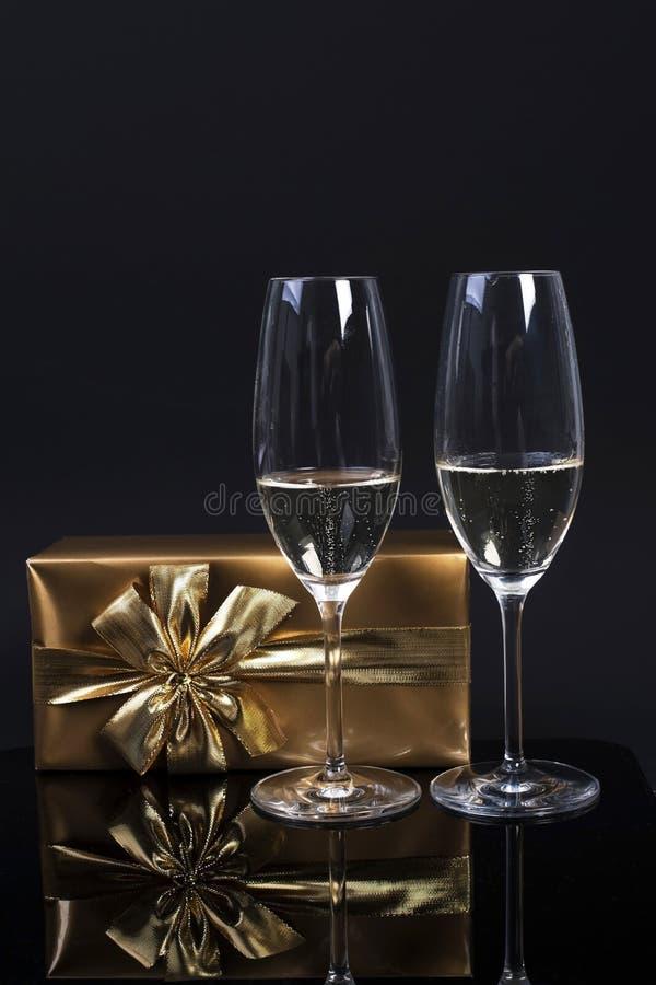 Due vetri con champagne, un regalo in carta dell'oro con un arco e una maschera di carnevale su un fondo nero fotografia stock
