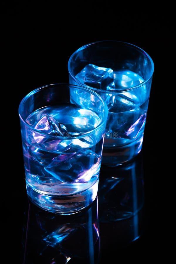 Due vetri con vodka ed i cubetti di ghiaccio contro lo - Lo specchio scuro ...