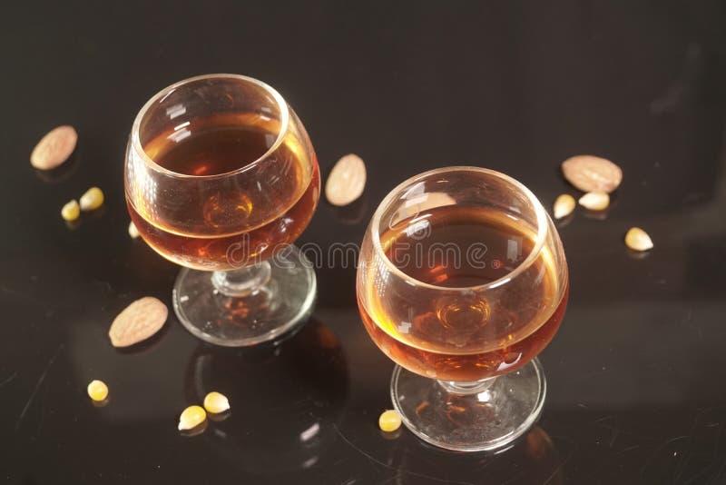 Due vetri del cognac su fondo nero con le mandorle immagine stock