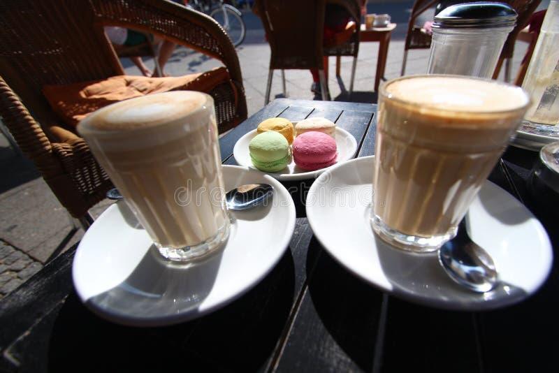Due vetri del macchiato del latte con il dessert del francese del macaron fotografia stock libera da diritti
