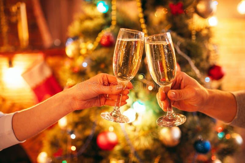 Due vetri del tintinnio delle mani con champagne, natale fotografia stock