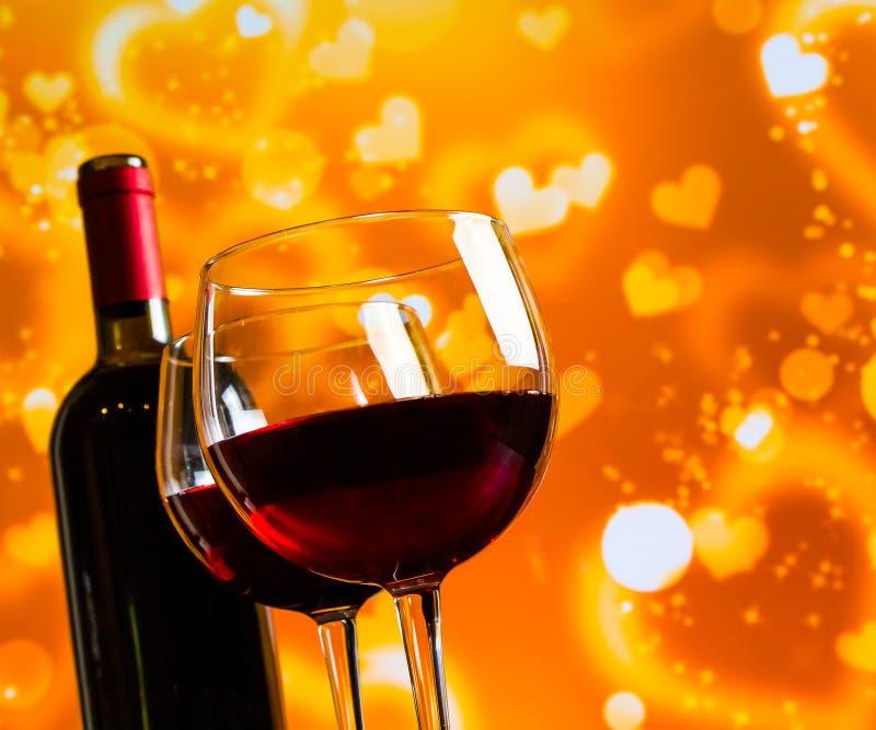 Due vetri del vino rosso contro il bokeh dorato dei cuori accende il fondo immagini stock libere da diritti