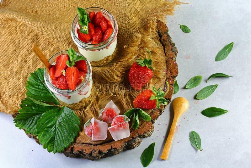 Due vetri del yogurt fresco sano della fragola con le bacche, i biscotti di farina d'avena cucchiaio di legno e la menta freschi, fotografie stock
