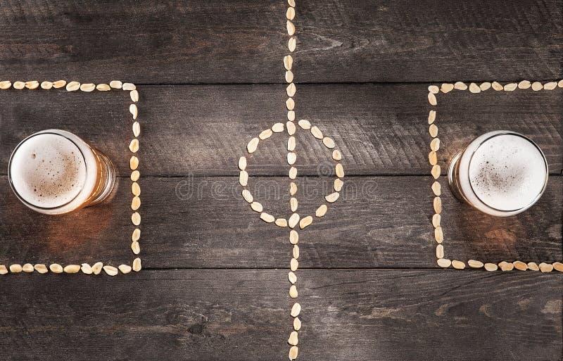 Due vetri di birra sulle marcature miniatura del campo di football americano dell'arachide fotografia stock libera da diritti