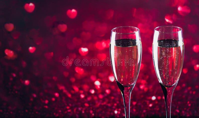 Due vetri di champagne con il bokeh rosso di forma del cuore su fondo immagini stock libere da diritti