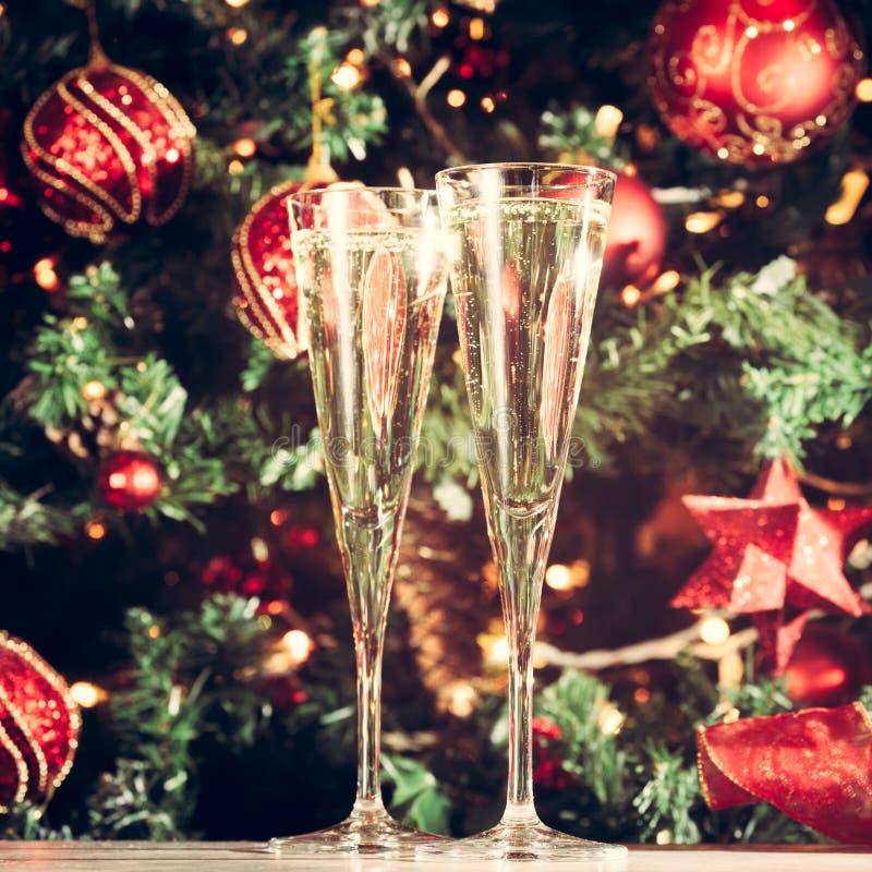 Due vetri di champagne con il fondo dell'albero di Natale festa immagini stock libere da diritti