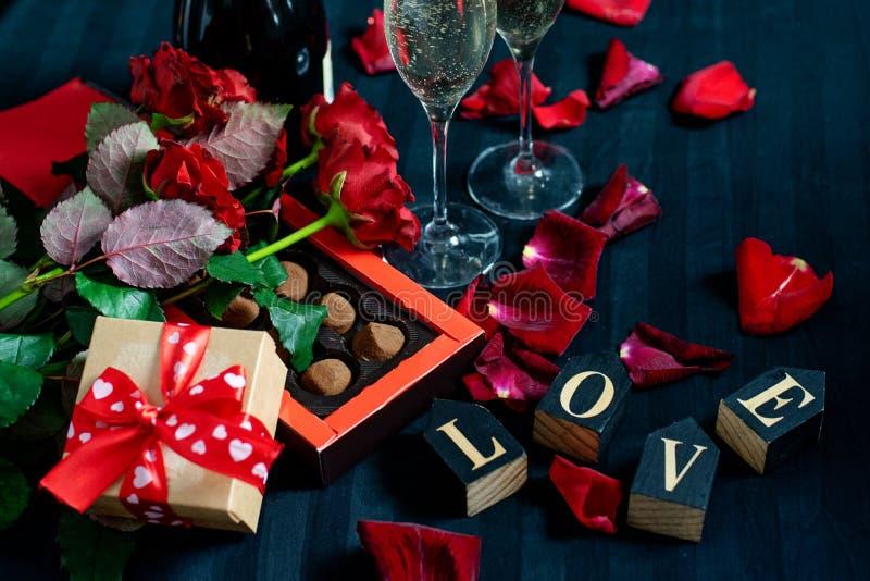 Due vetri di champagne, delle rose rosse, dei petali, del contenitore di regalo con il nastro rosso, del cioccolato e delle parol fotografie stock libere da diritti