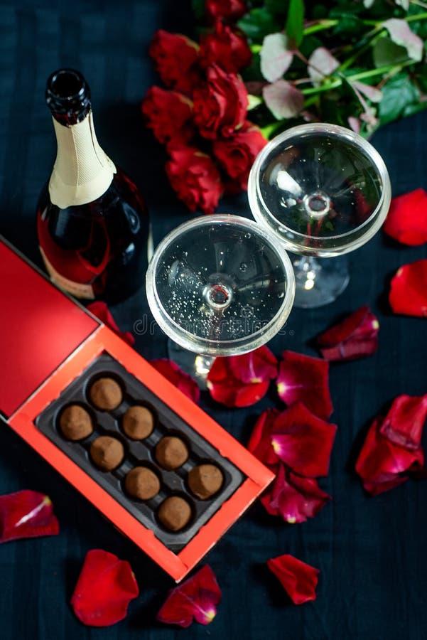 Due vetri di champagne, delle rose rosse, dei petali e del cioccolato su un fondo nero fotografie stock