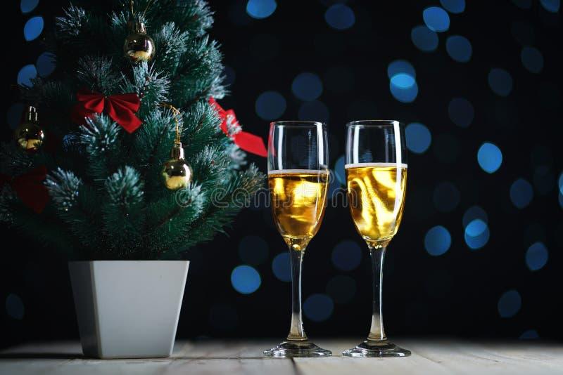 Due vetri di Champagne e di piccola incandescenza scura Ligh dell'albero di Natale fotografia stock libera da diritti