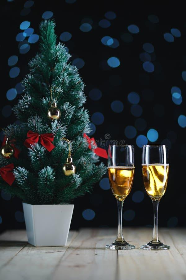 Due vetri di Champagne e di piccola incandescenza scura Ligh dell'albero di Natale immagini stock