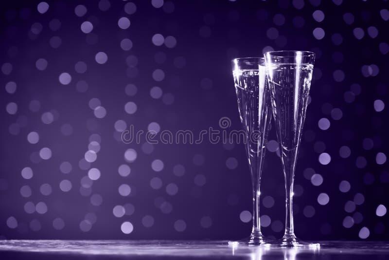 Due vetri di champagne sul fondo scuro del bokeh Ultravioletto fotografie stock libere da diritti