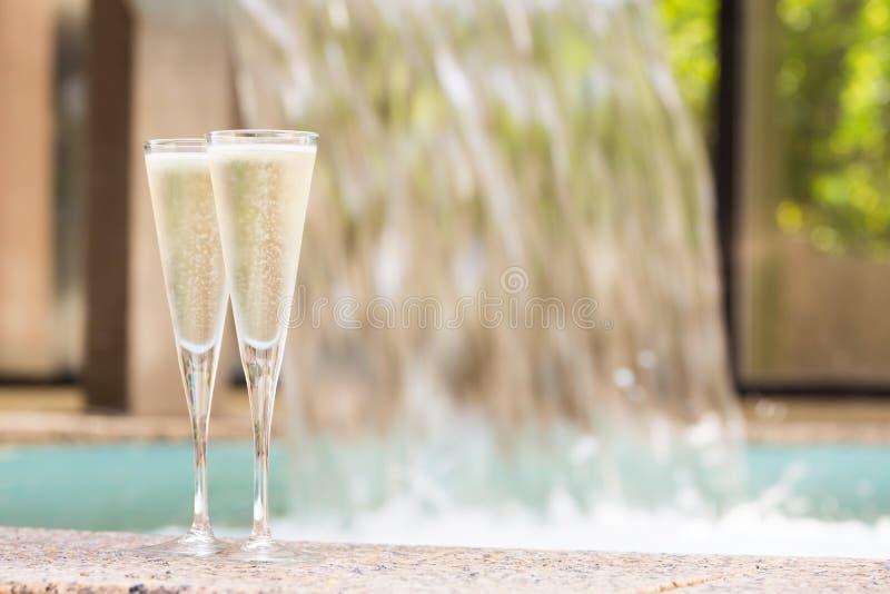 Due vetri di champagne vicino alla Jacuzzi all'aperto immagine stock