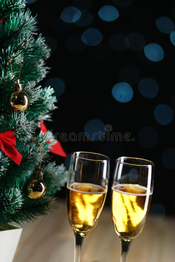 Due vetri di incandescenza scura L di Champagne Beside Small Christmas Tree fotografia stock libera da diritti