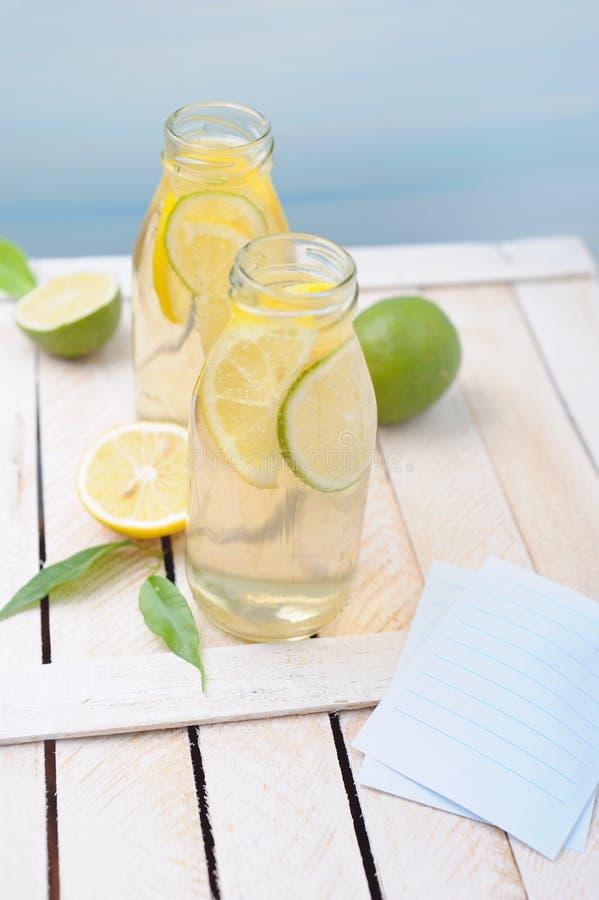 Due vetri di limonata con il limone fresco sulla tavola rustica fotografia stock