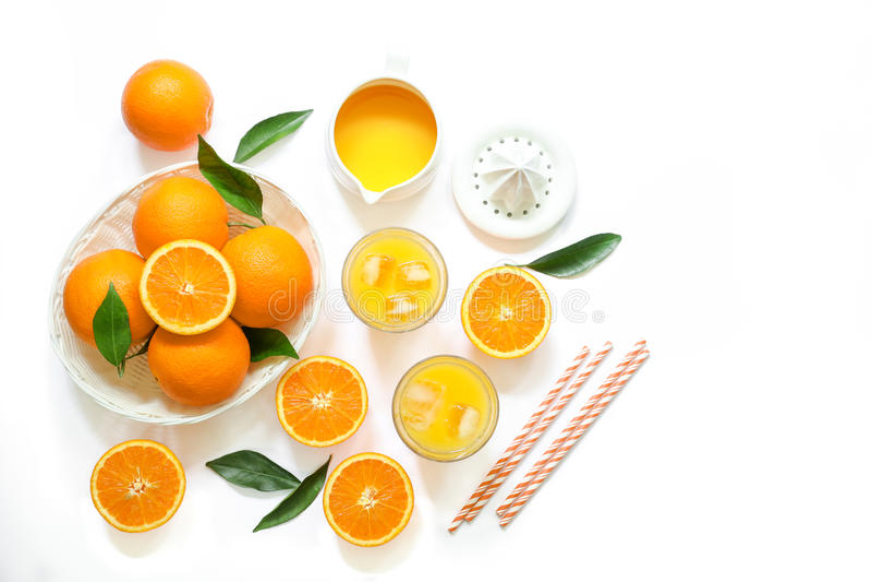 Due vetri di succo d'arancia con i cubetti di ghiaccio e le arance isolati sulla vista superiore del fondo bianco fotografie stock libere da diritti