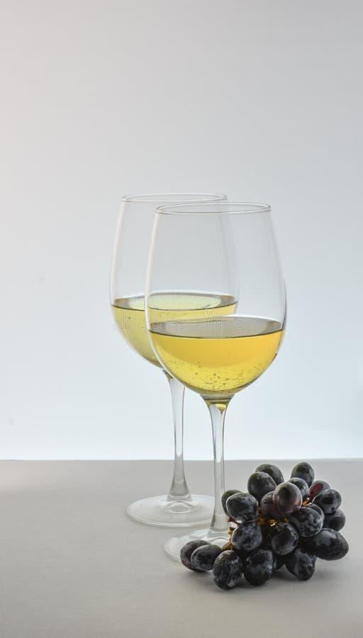 Due vetri di vino bianco con l'uva immagini stock